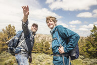 Father and teenage son pointing out to landscape on hiking trip, Cody, Wyoming, USA - CUF15062