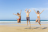 Man and two young women wearing swimwear jumping on beach, El Cotillo, Fuerteventura, Spain - CUF15080