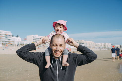 France, La Baule, portrait of father carrying his little daughter on shoulders on the beach - GEMF02031