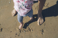 Baby girl learning to walk with her father on the beach, partial view - GEMF02037