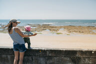 France, mother and baby girl having fun together at beach promenade - GEMF02040
