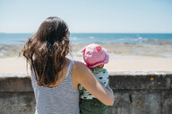 France, back view of mother and baby girl looking to the sea - GEMF02043