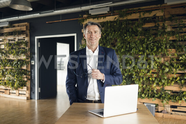 Portrait of confident mature businessman with laptop in green office - JOSF02193
