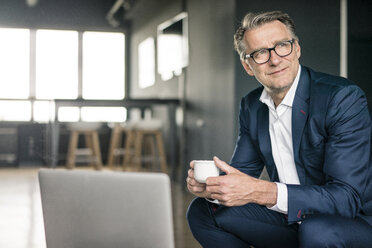 Smiling mature businessman with cup of coffee thinking - JOSF02196