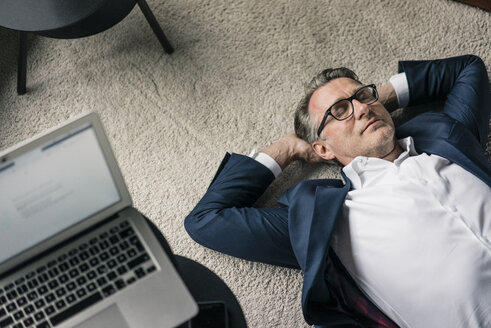 Mature businessman lying on carpet next to laptop - JOSF02199