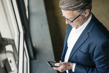 Mature businessman standing at the window using cell phone - JOSF02211