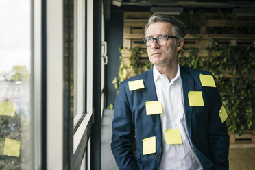 Serious mature businessman covered with sticky notes looking out of window - JOSF02220
