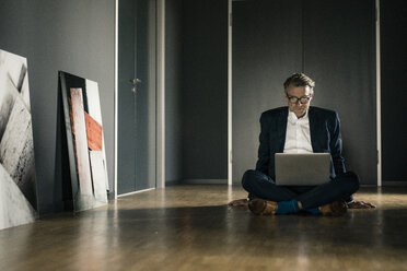 Mature businessman using laptop on office floor - JOSF02223