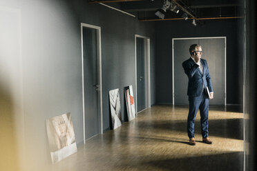 Mature businessman standing on office floor with paintings using cell phone - JOSF02226