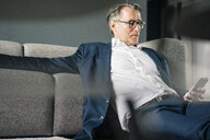 Mature businessman sitting on couch using cell phone - JOSF02232