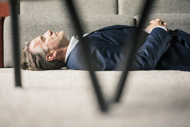 Mature businessman lying on carpet with closed eyes - JOSF02235