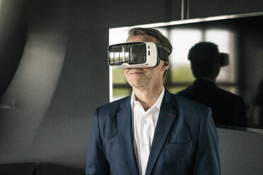 Mature businessman wearing VR glasses in office - JOSF02241