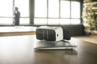 VR glasses and laptop on table in office with businessman in background - JOSF02271