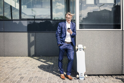 Mature businessman using cell phone outdoors next to longboard - JOSF02286