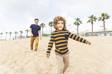 Spain, Barcelona, father and son walking on the beach - WPEF00356