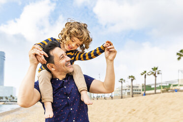 Spain, Barcelona, father with son on the beach giving a piggyback ride - WPEF00359
