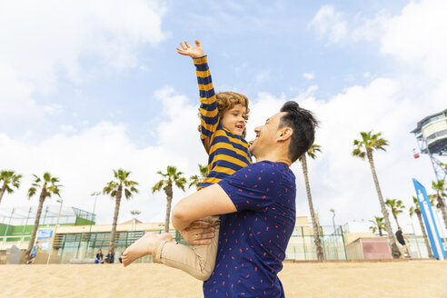 Spain, Barcelona, happy father and son on the beach - WPEF00374