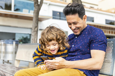 Spain, Barcelona, happy father and son with a smartphone sitting on bench - WPEF00377