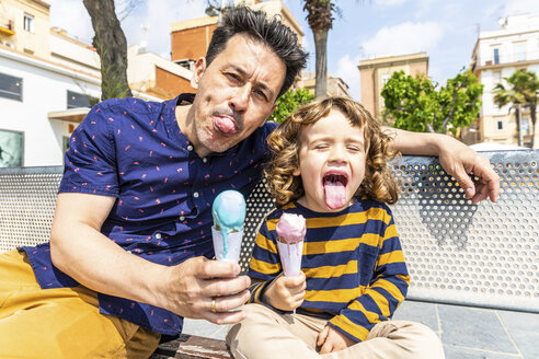 Spain, Barcelona, happy father and son sitting on bench enjoying an ice cream - WPEF00380
