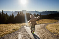 Rear view of female toddler toddling on sunlit dirt track, Tegernsee, Bavaria, Germany - CUF15113
