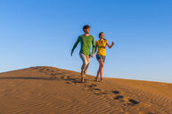 Romantic mid adult couple running on sand dunes at sunset, Maspalomas, Gran Canaria, Canary Islands, Spain - CUF15122