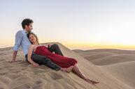 Romantic mid adult couple reclining on steep dunes, Maspalomas, Gran Canaria, Canary Islands, Spain - CUF15128