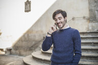 Young man in front of stone steps using smartphone smiling - CUF15281