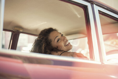 Young woman on road trip looking over shoulder through vintage car window, Cape Town, South Africa - CUF15293