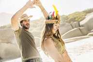 Mid adult couple wearing straw hat and feather headdress dancing on beach, Cape Town, South Africa - CUF15326