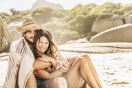 Romantic mid adult couple wrapped in blanket sitting on beach, Cape Town, South Africa - CUF15332