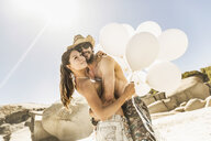 Couple holding bunch of balloons hugging on beach, Cape Town, South Africa - CUF15338