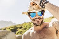 Portrait of man wearing blue mirrored sunglasses and straw hat on beach, Cape Town, South Africa - CUF15341