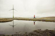 Runner jogging on wind farm, Eysturoy, Faroe Islands - CUF15359