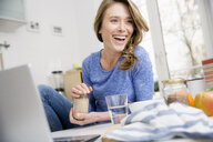 Happy woman sitting at kitchen table using laptop - CUF15398