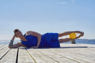 Man lying on side on pier, resting on elbow ball between legs looking at camera - CUF15431