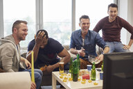 Group of men watching sports event on television with snacks and beers smiling - CUF15440