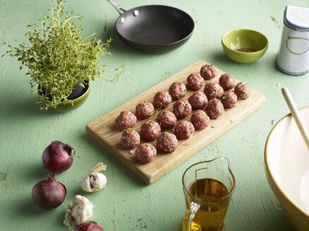 Rows of raw prepared greek meatballs on chopping board - CUF15521