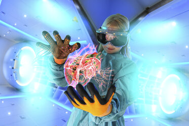 Girl in virtual reality headset interacting with digital floating human heart - CUF15674