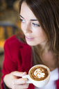 Close up of young woman with cappuccino in cafe - CUF15842