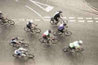Overhead view of eight cyclists speeding on urban road in racing cycle race - CUF15944