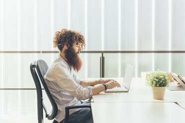 Young male hipster with red hair and beard typing on laptop at desk - CUF16022