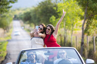 Two young female friends taking selfie whilst driving on rural road in convertible, Majorca, Spain - CUF16097