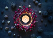 Overhead view of burning candle surrounded by berry wreath and nuts - CUF16118