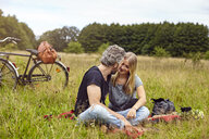 Romantic couple sitting on picnic blanket in rural field - CUF16274