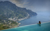 Rear view of woman looking out to coast from infinity pool, Ravello, Amalfi coast, Italy - CUF16292