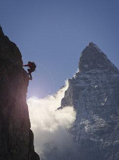 Silhouetted female climber climbing rock face near Matterhorn, Canton Wallis, Switzerland - CUF16295
