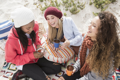 Three young women laughing on beach picnic, Western Cape, South Africa - CUF16346