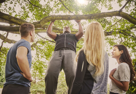 Personal trainer demonstrating pull ups on park tree branch - CUF16364