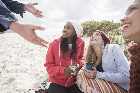 Young women and man picnicking on beach, Western Cape, South Africa - CUF16370