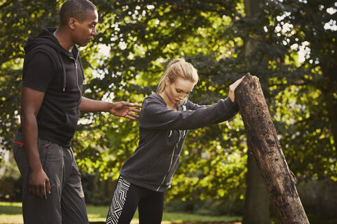 Young woman with personal trainer lifting tree trunk in park - CUF16379